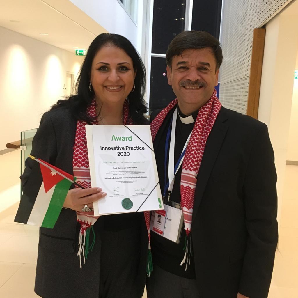 Pfr. Samir Esaid und seine Frau, Schulleiterin Sabah Zurikat, freuen sich und halten die Gewinnerurkunde und eine jordanische Flagge ins Bild.